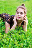 Girl laying in bright green grass Stock Photos