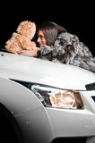 Girl laying on car hood with plush toy Stock Photo