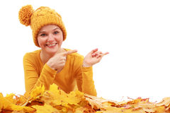 Girl laying in colored autumn leaves and showing to the right. On white background royalty free stock photography