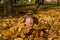 Girl laying in colorful leaves Royalty Free Stock Photos