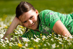 Girl laying on the daisy flowers field Stock Photos