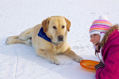 Girl laying with dog in snow Royalty Free Stock Images