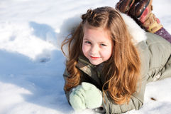 Girl laying down in the snow Royalty Free Stock Image