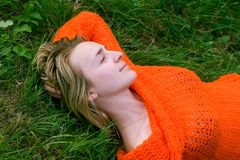 Girl laying on the grass. In the orange sweater royalty free stock image