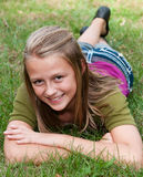 Girl Laying in the Grass. Pretty teenage girl poses prone on the grass Royalty Free Stock Photo