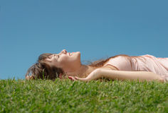 The girl laying on a grass Stock Images