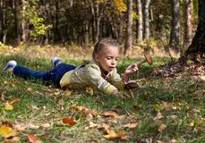 A girl is laying on a grass in the forest Stock Photography