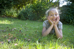 Girl laying on grass with head in hands Stock Image