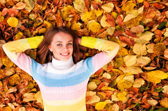 Girl Laying On A Heap Of Yellow Leaves Stock Photos