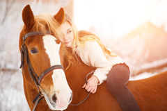 Girl laying on horse neck. Friendship background Royalty Free Stock Image
