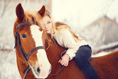 Girl laying on horse neck. Friendship background Stock Image