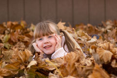 Girl laying in leaf pile play playing Royalty Free Stock Images