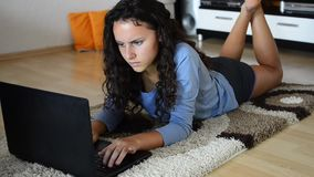 Girl laying in living room and using laptop stock footage