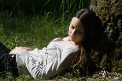 The girl laying near a tree. The girl sleeping near a tree Royalty Free Stock Photography