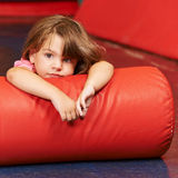 Girl laying on pillow in gym Royalty Free Stock Image