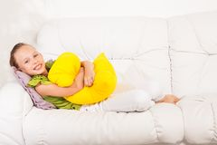 Girl laying with pillow Stock Images