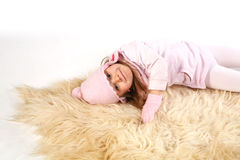Girl laying on rug Stock Images