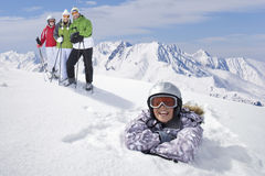 Girl laying in snow with family of skiers standing near on mountain top Royalty Free Stock Photography
