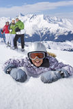 Girl laying in snow with family of skiers standing near on mountain top Stock Image