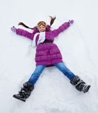 Girl laying in star shape in snow Stock Images
