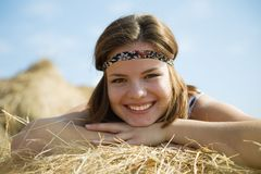 Girl laying on straw bail Royalty Free Stock Photos
