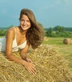 Girl laying on straw bail Stock Images