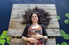 Girl laying on wooden bridge Stock Image