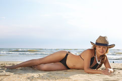 Girl lays on a beach in a hat Royalty Free Stock Images