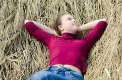 Girl lays on a dry grass Royalty Free Stock Photo