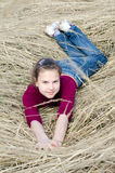 Girl lays on a dry grass outdoor Stock Photography