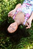 The girl lays on a grass a meadow. Summer time royalty free stock image