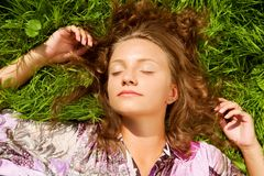 The girl lays on a grass a meadow. Summer stock photos