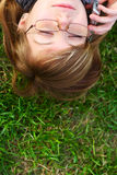 The girl lays on a grass with phone. Lifestyles royalty free stock image