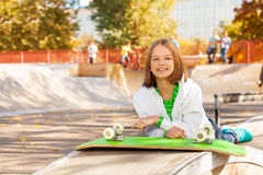 Girl lays near green skateboard with wheels up Royalty Free Stock Image