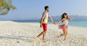 Girl leading man to water, couple holding hands walking on beach, happy smiling tourists on sea vacation. Slow motion 60 stock video footage