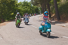 Girl leads a group of bikers riding a vintage italian scooter Royalty Free Stock Photography
