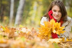Girl upon leafed ground. Image of pretty girl lying on ground covered with yellow dry leaves in fall stock images