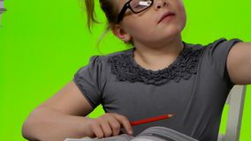 Girl leafing through a book of interesting looks for another. Green screen. Close up stock footage