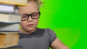 Girl leafing through a book of interesting looks for another. Green screen. Close up stock video footage
