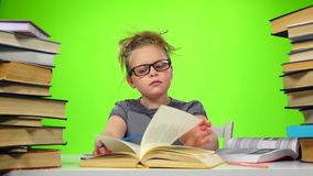 Girl leafing through the pages of books carefully. Green screen. Slow motion stock video