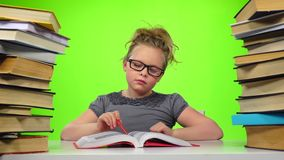 Girl leafing through the pages of books carefully. Green screen. Slow motion stock video footage
