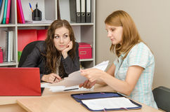 Girl leafing through paper documents at the reception office specialist Stock Photography