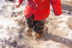 Girl in leahther boots black pants and red jacket standing in a puddle of water splashes snow and ice on warm winter day Royalty Free Stock Photos