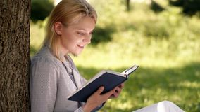 Girl lean on tree while relax in park sit grass. Self improvement book. Self improvement and education concept. Business. Lady find minute to read book improve stock video footage