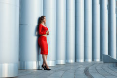 Girl leaned against the column. She is trendy red suit. Stock Image