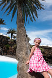 Girl leaned against a palm tree Royalty Free Stock Image