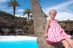 Girl leaned against a palm tree Royalty Free Stock Images