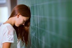 Girl leaned her head on the blackboard Stock Photography