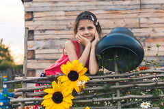 The girl leaned on the wicker fence. Girl leaned on the fence next braided with flowers and a large cast-iron cauldron Stock Photos