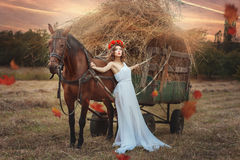 Girl is leaning against the transport of hay. Royalty Free Stock Photos